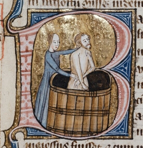 medieval illustration of a man bathing in a wooden bath