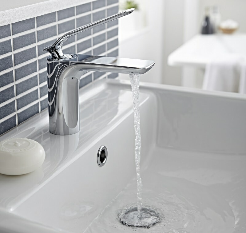 water flowing from a modern basin tap into basin