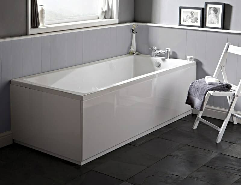 White rectangular bath with slate tile floor and grey wood panel walls