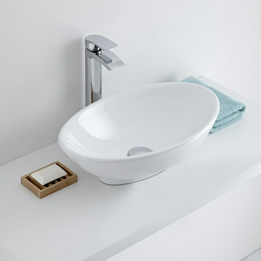 Small oval countertop basin with counter top mounted mono tap