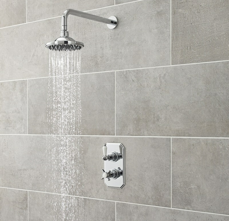 water flowing from a round shower head with chrome arm