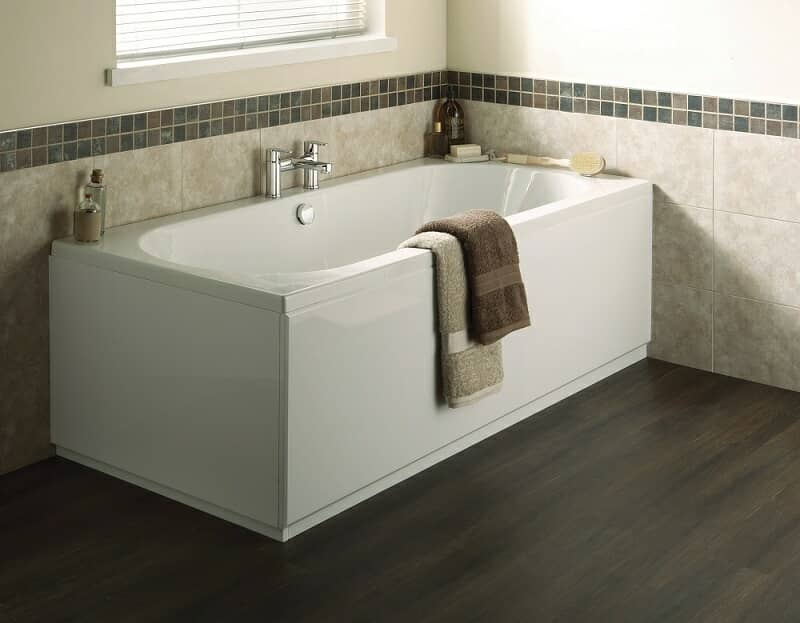 Rectangular bath with white panels and brown towels, tiles and floor