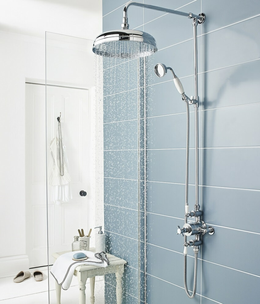 traditional shower against a blue tiled wall