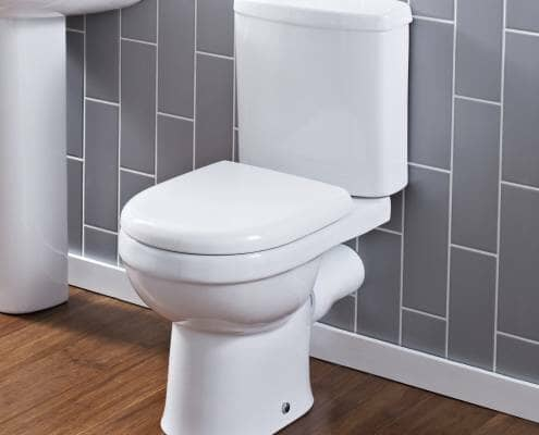 modern close coupled toilet against a grey tiled wall