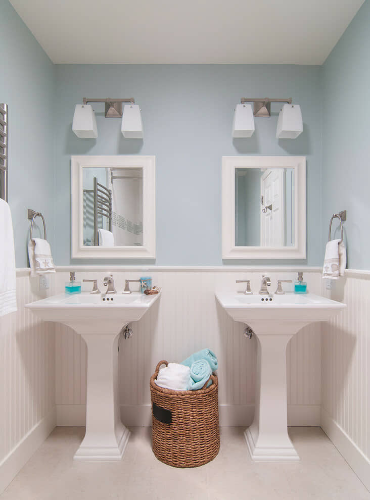 Wicker basket between twin pedestal basins in duck egg blue bathroom