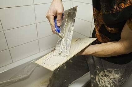 A man tiling a new bathroom