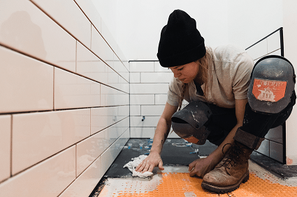 A woman removing the flooring during a bathroom renovation