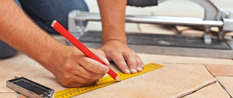 Man using ruler and red pencil to mark a floor tile