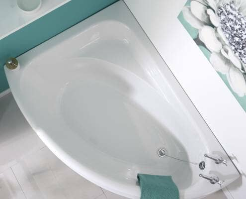 corner bath against a turquoise wall