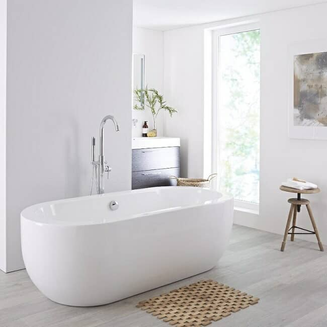 White, oval shaped, flat topped, modern freestanding bath with freestanding deck mounted tap