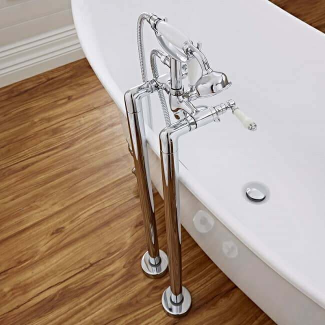 Chrome freestanding-bath-tap with white tap handles and traditional shower handset over a freestanding bath
