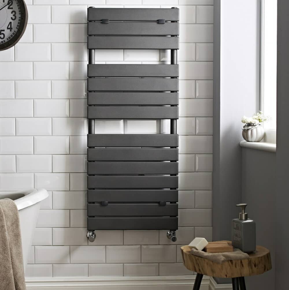 Grey heated towel rail on white metro tiled wall with grey adjacent wall.