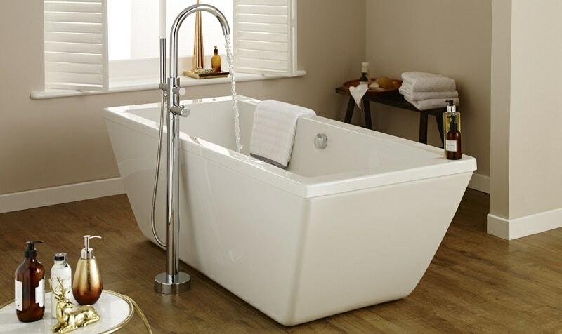 White rectangular freestanding bath in a neutral white and wood bathroom