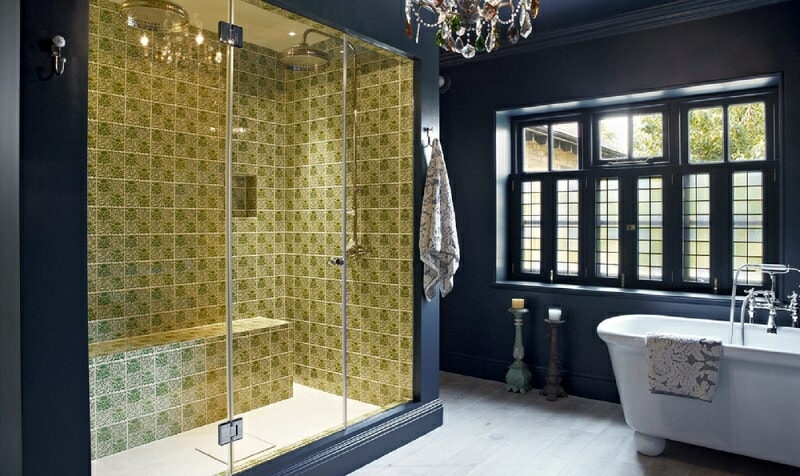 Dark blue bathroom with golden-yellow tiled shower area