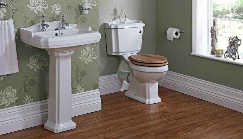 Traditional pedestal basin with traditional design toilet and wooden toilet seat