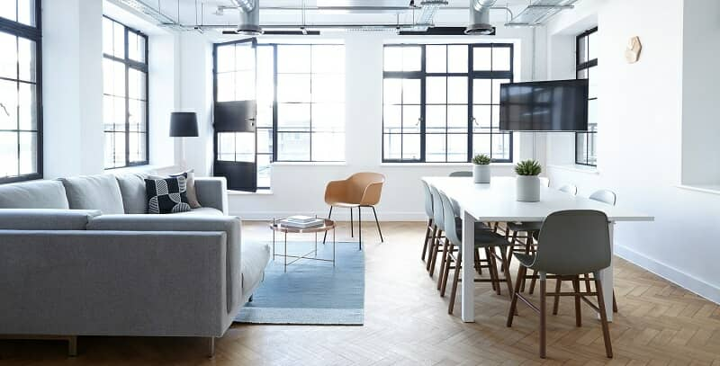 Modern office with table, chaires, corner sofa and large windows.