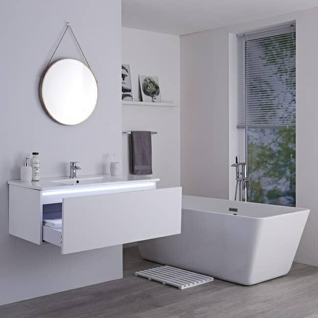 white bathroom with rectangular freestanding bath and illuminated vanity unit
