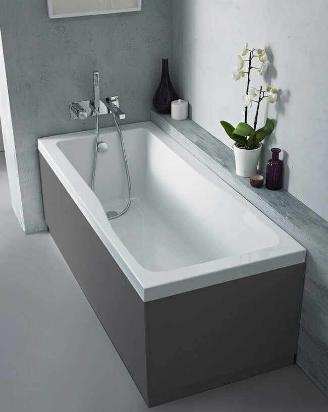 bath with grey panels in light grey room.