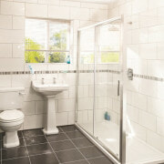 bathroom suite with shower, toilet and basin, black tiled floor