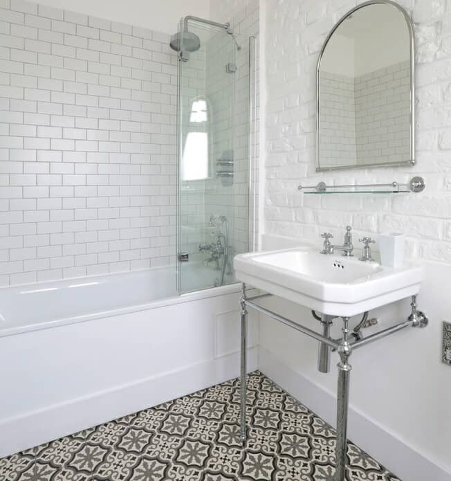 Bath and basin with pattered bathroom floor tiles and white brick wall