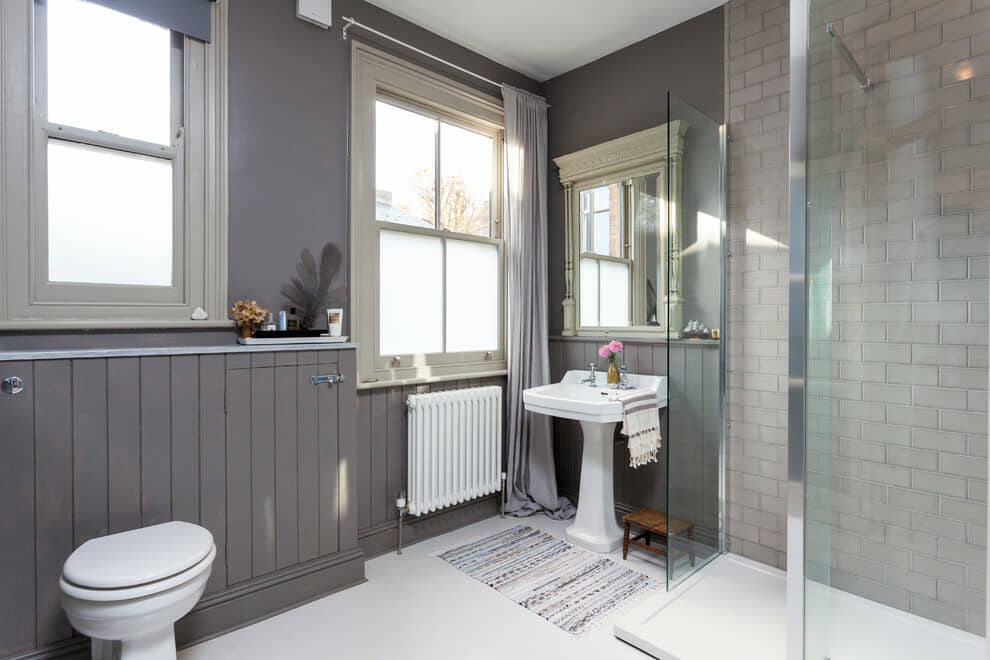 Bathroom with Grey painted wood panels and walls.