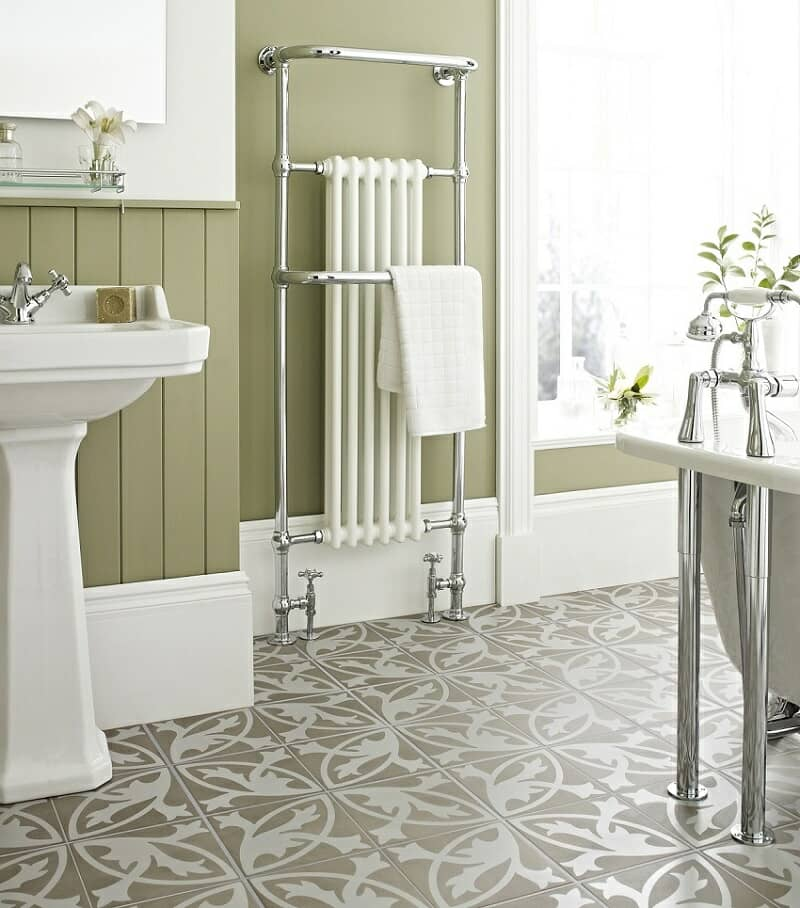 Green bathroom with white furnishings and beige-white patterned tiles with a traditional design