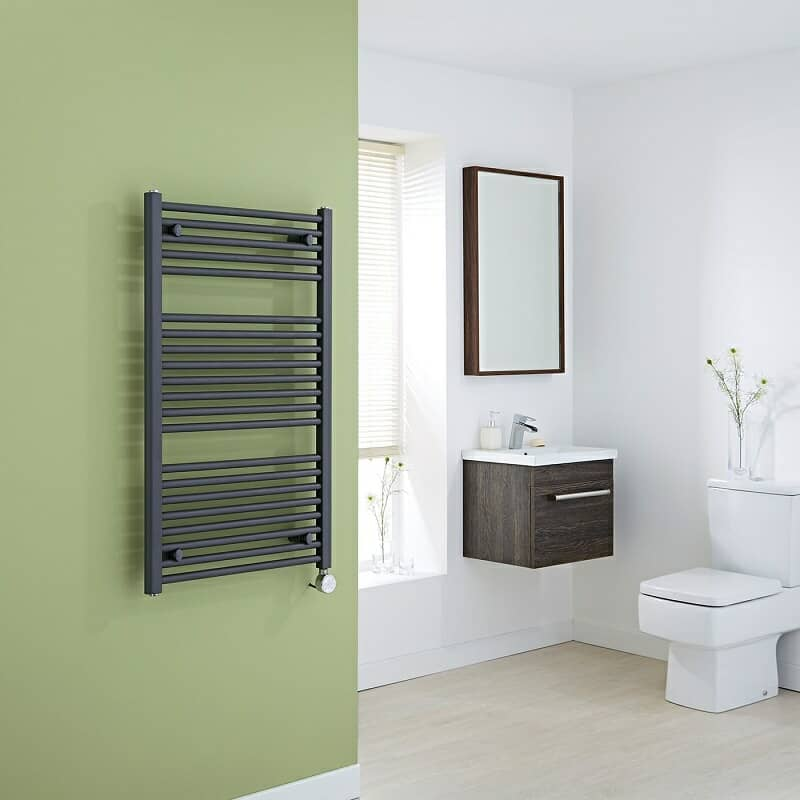 Anthracite electric heated towel rail on green wall in white bathroom