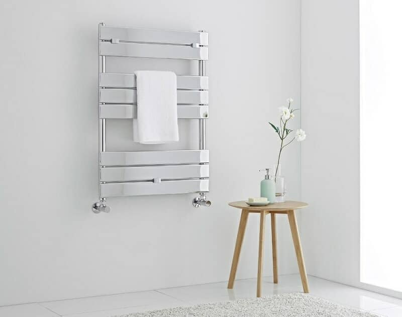 Chrome heated towel rail with white towel and wooden stool