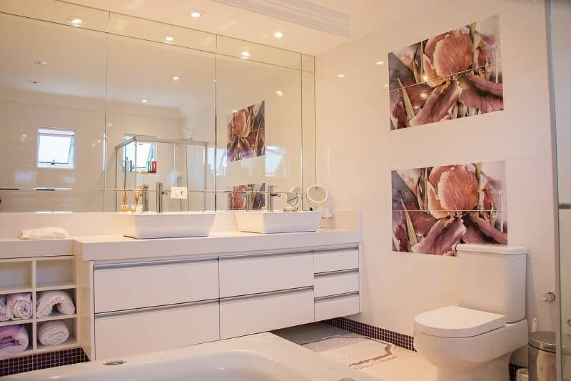 Well lit bathroom with white units and mirrors and small LED spot lights.