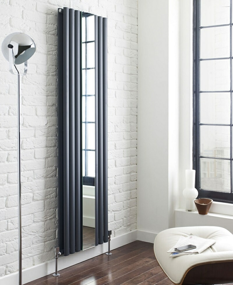 Anthracite vertical designer radiator with vertical mirror on white brick wall in modern apartment