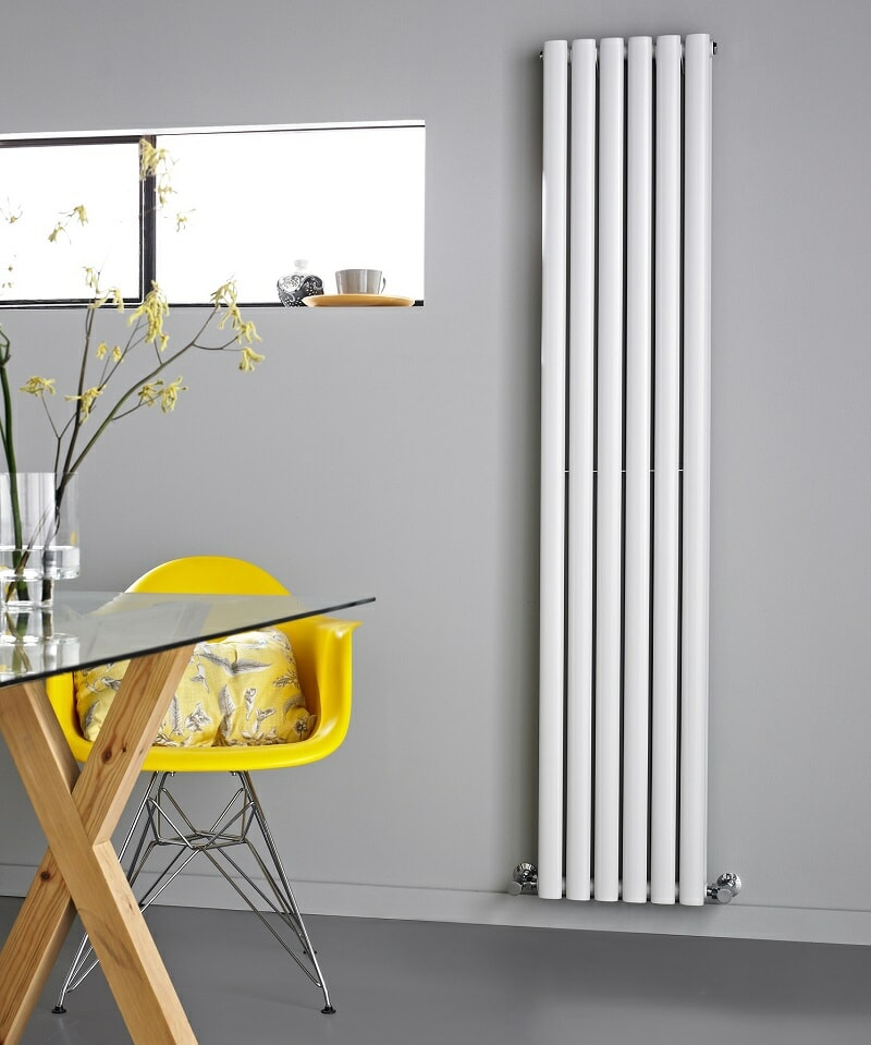 White vertical designer radiator on grey wall with yellow designer chair and glass table