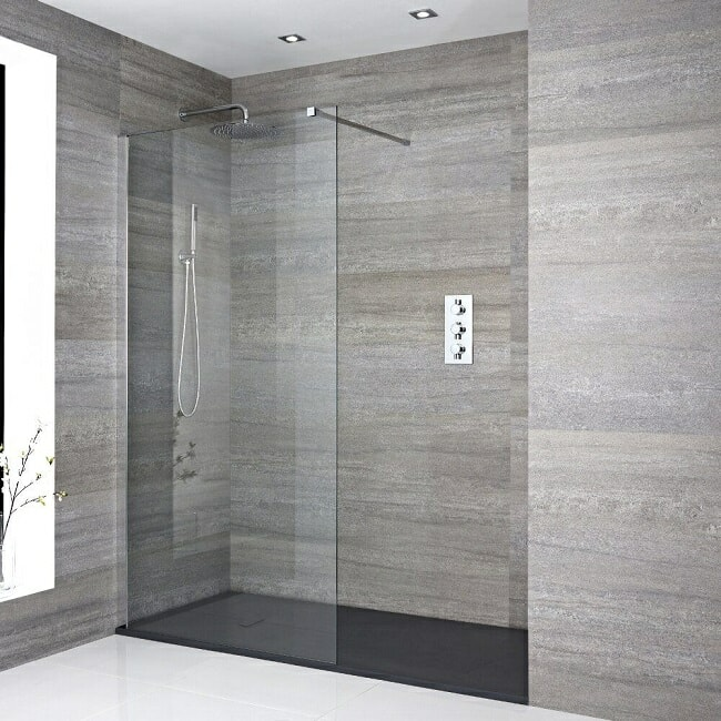 Recessed walk in shower with round chrome shower head and arm, glass screen, and black shower tray