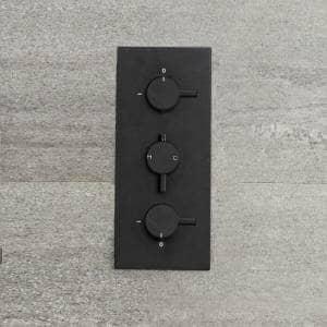 a black shower valve on a bathroom wall