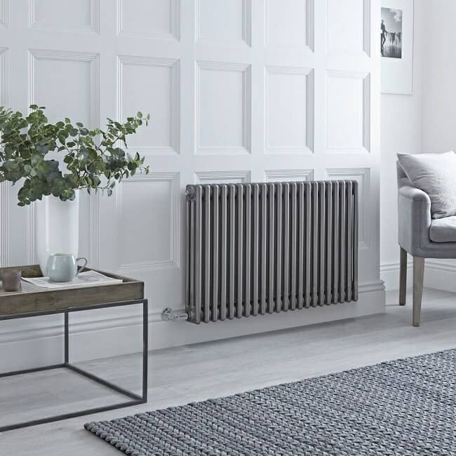 Raw metal lacquered finish column radiator in white traditional room with grey accents