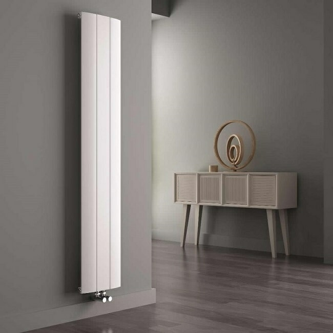 white vertical designer radiator in grey room with natural furniture