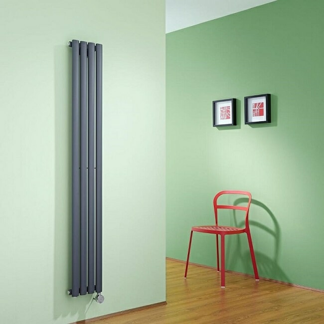Anthracite Milano vertical radiator with electric element in green room with red chair