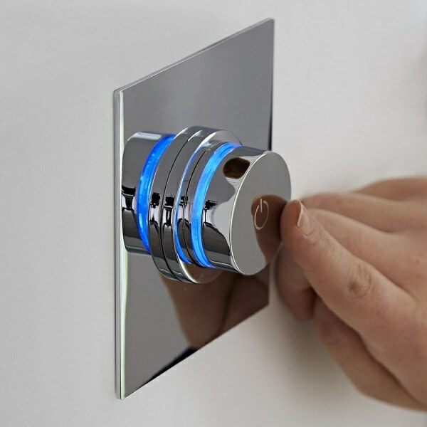 Blue illuminated digital shower push button control being pressed