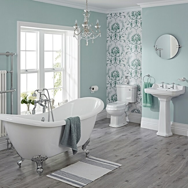 Traditional bathroom suite with freestanding bath, toilet and cistern, and pedestal basin, with round mirror.
