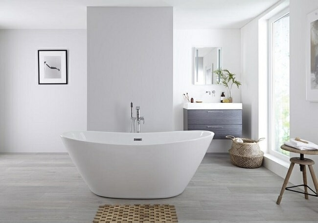 Modern curved freestanding bath in the middle of a large minimalist bathroom with vanity unit and mirror cabinet