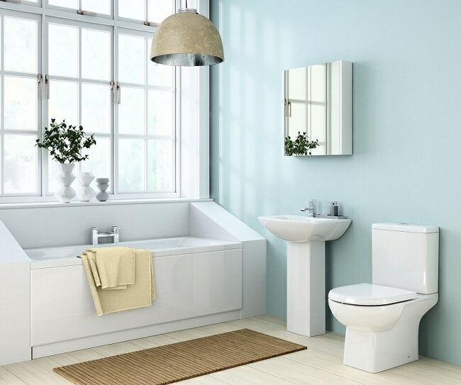 Modern angular bathroom with rectangular bath under window, pedestal sink, and toilet with cistern