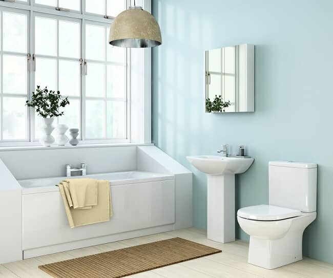Modern angular bathroom with rectangular bath under window, pedestal sink, and toilet with cistern