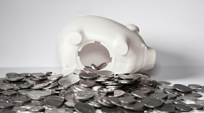 Open piggy bank with silver coins spilling out