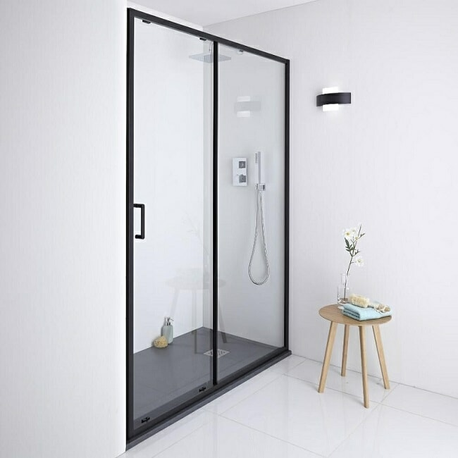 Recess shower with black-framed sliding shower door and shower tray