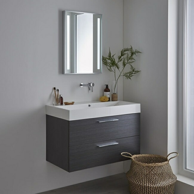 illuminated bathroom mirror with wall hung vanity unit and tap