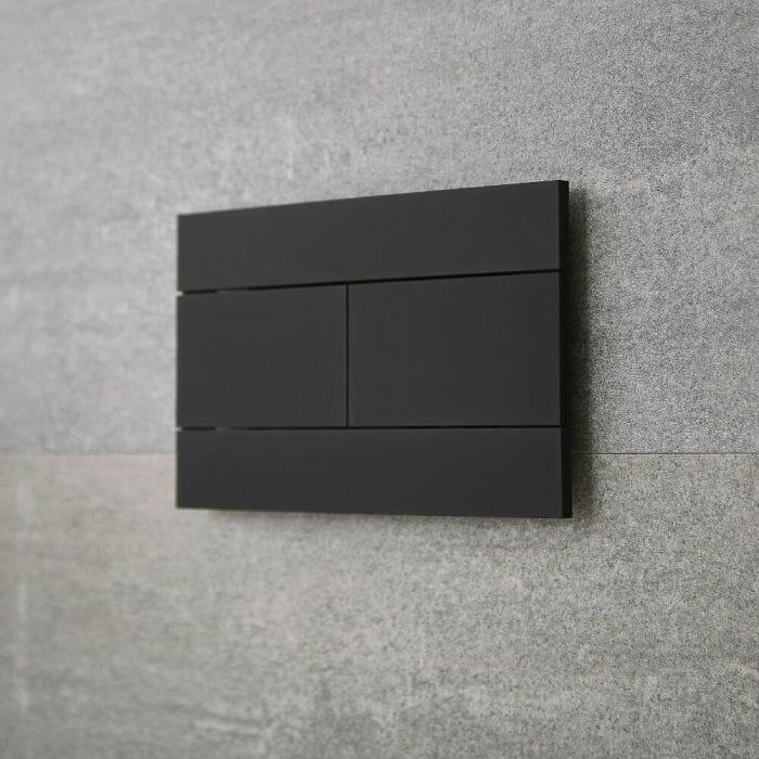 a matt black toilet flushplate on a grey bathroom wall