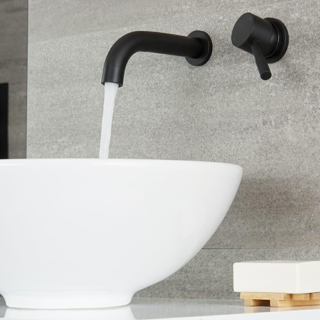 Milano Nero wall mounted basin mixer with water flowing into a basin