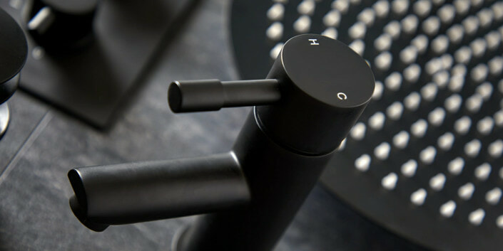 close up of a black basin tap in front of a black shower head