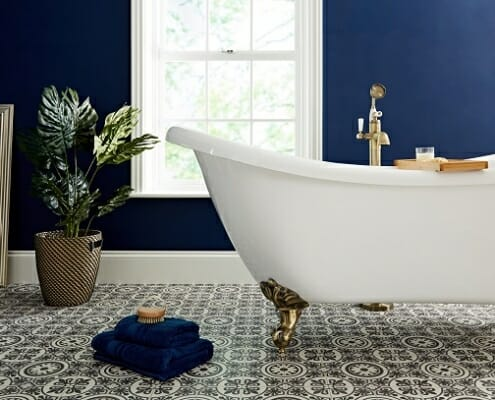 A white freestanding bathtub and gold bath tap in a blue bathroom