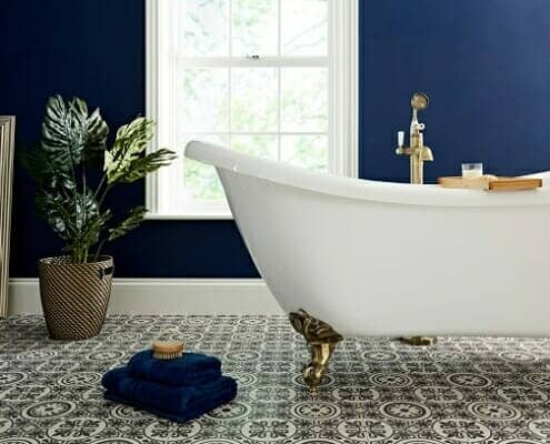 A white freestanding bathtub and gold bath tap in a blue bathroom