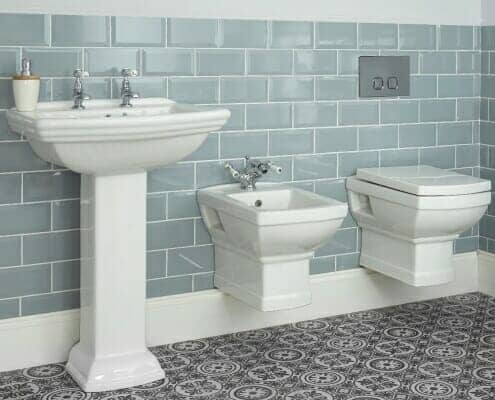 A traditional basin toilet and bidet combination in a traditional country bathroom space